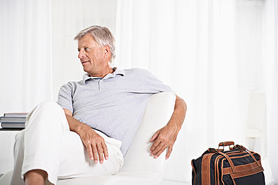 Spain, Senior man waiting in lobby with suitcase - p300m752798f by Philipp Dimitri (Coop)