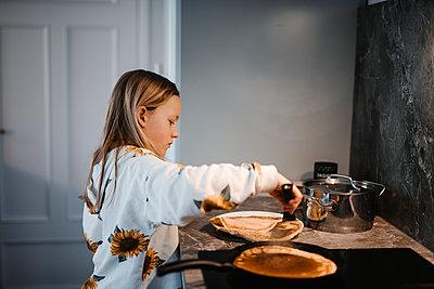 Girl in kitchen preparing pancakes - p312m2237227 by Anna Johnsson