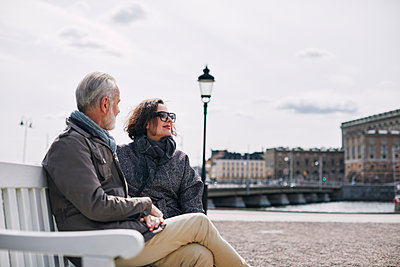 Couple relaxing on bench - p312m2299556 by Plattform