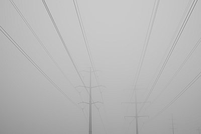 Electrical wires sit high in the fog. - p343m801021f by Joel Addams