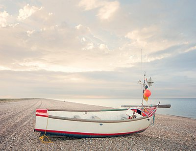 Fishing boat on empty shingle beach, Norfolk, England, UK - p429m1047104 by Craig Easton