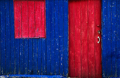 A painted red door and window cover on a blue wooden building; st abb's head scottish borders scotland - p442m719205f by John Short