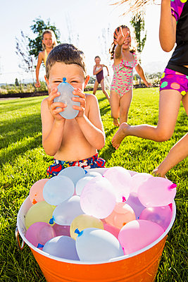 Caucasian children playing with water balloons in backyard - p555m1415626 by Mike Kemp