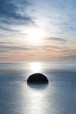 A single Moeraki Boulder at sunrise with long exposure, Moeraki Beach, Otago, South Island, New Zealand - p871m2068620 by Ed Rhodes