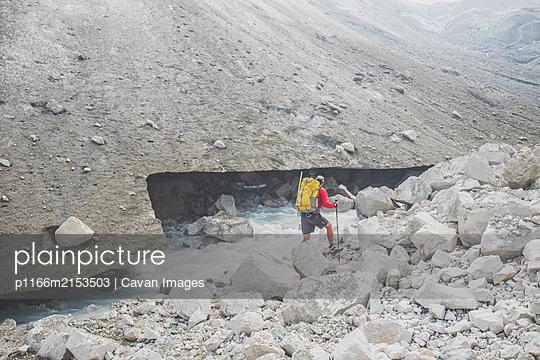 Backpacker hiking beside melting glacier. - p1166m2153503 by Cavan Images