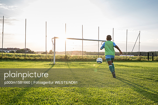 Young football player on football ground at sunset - p300m1581660 von Fotoagentur WESTEND61