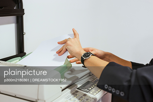 Close-up of businesswoman taking papers from printer in office - p300m2180361 by DREAMSTOCK1982
