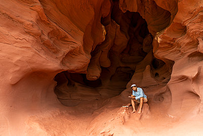 Young man sitting in a cave, taking notes - p300m2059800 by VITTA GALLERY