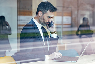 Serious businessman using laptop while talking on phone at office - p300m2282120 by Josep Suria
