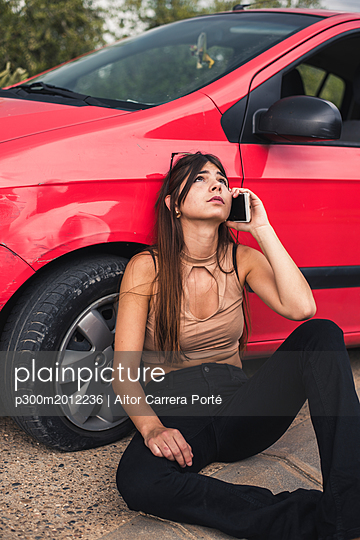 Young woman sitting at roadside having a car breakdown calling breakdown service - p300m2012236 von Aitor Carrera Porté