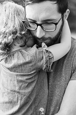 Black and white close up of a millennial father comforting daughter - p1166m2218603 by Cavan Images