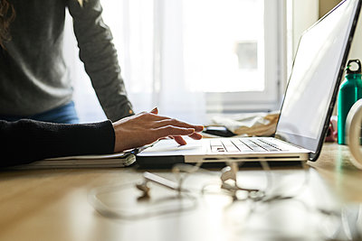 Close-up of two women using laptop at desk at home - p300m1588011 von Josep Rovirosa