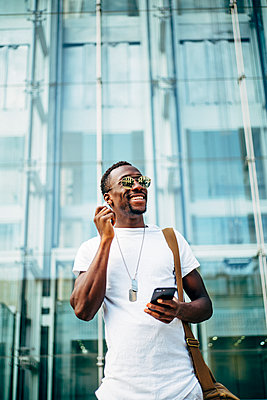 Happy young man with mobile phone in the city putting in earphones - p300m2132320 by Oscar Carrascosa Martinez