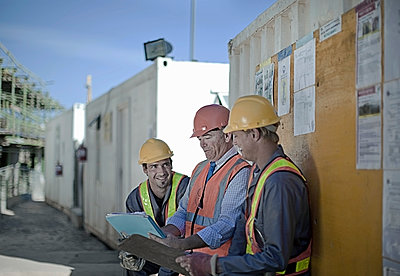 Construction workers discussing plans on construction site, Cape Town, South Africa - p300m2250292 von LOUIS CHRISTIAN