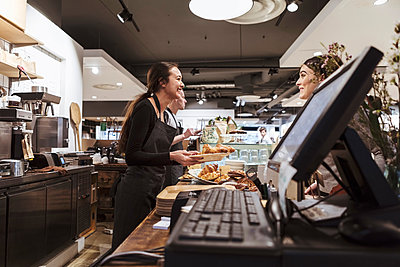 Saleswoman serving food to customer at cafe - p426m2035335 by Kentaroo Tryman