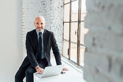 Portrait of businessman sitting on windowsill using laptop - p429m1578574 by Eugenio Marongiu