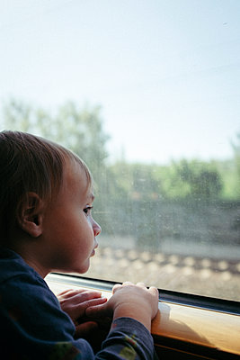 Baby boy gazing out train window - p795m2223679 by JanJasperKlein