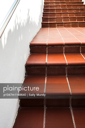 Red tiled steps next to white wall with handrail - p1047m1169640 by Sally Mundy