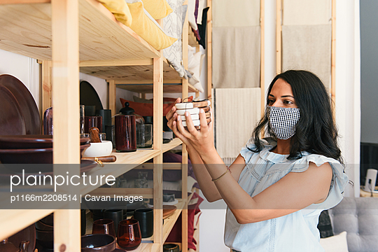 Masked up woman inspecting coasters at luxury home goods store - p1166m2208514 by Cavan Images