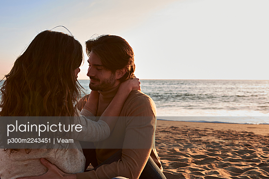 Girlfriend and boyfriend with arm around sitting face to face on beach - p300m2243451 by Veam
