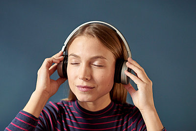 Young woman listens to music with headphones - p1124m1589225 by Willing-Holtz