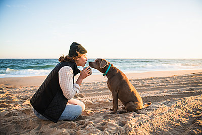 Young woman enjoying drink in mug while beach car camping with dog - p1166m2285583 by Cavan Images