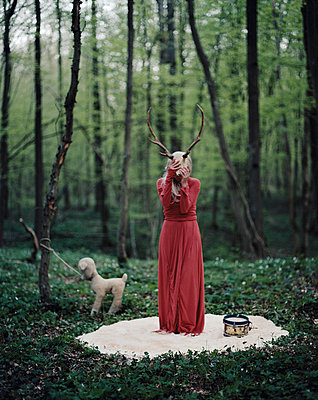 Woman with antlers over face in the forest - p1270m1114200 by Elene Usdin