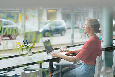 Young woman with cup of coffee and laptop sitting at the window in a cafe - p300m2059096 by Kniel Synnatzschke
