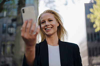 Smiling blond female professional on video call through smart phone in city - p300m2214001 by Joseffson