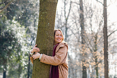 Smiling woman embracing tree at park - p300m2275078 by Emma Innocenti