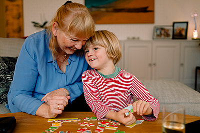 Smiling grandson and grandmother playing with jigsaw puzzle at home - p426m2195344 by Maskot