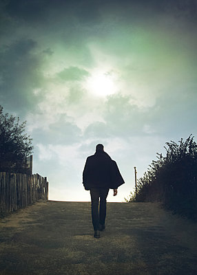 Man walking up Road - p984m1172284 by Mark Owen