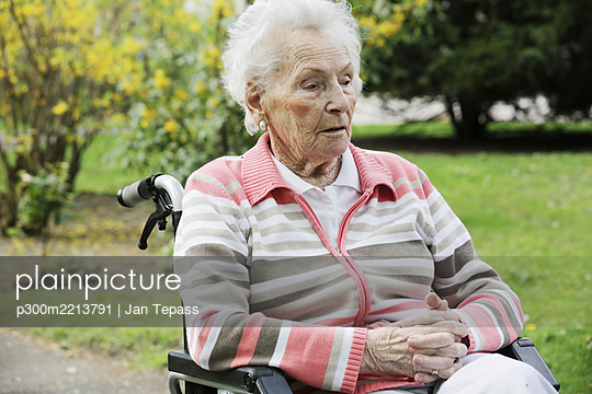 Germany, North Rhine Westphalia, Cologne, Senior woman sitting on wheelchair - p300m2213791 by Jan Tepass