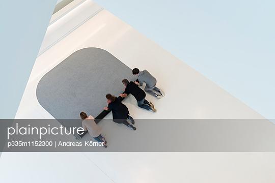 Gemeinsam einen Teppich ausrollen  - p335m1152300 von Andreas Körner