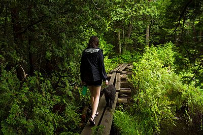 Rear view of woman with dog walking on boardwalk in forest - p1166m1518681 by Cavan Images