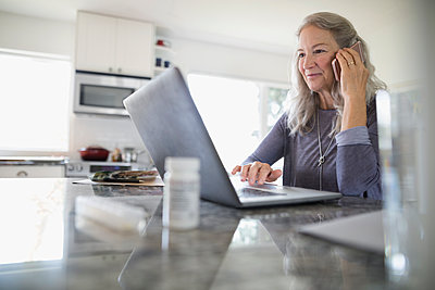 Senior woman talking on cell phone and using laptop in kitchen - p1192m1529640 by Hero Images