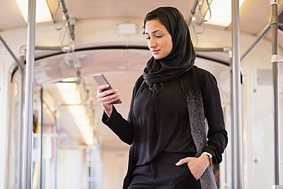 Young woman in hijab using mobile phone - p1315m1566090 by Wavebreak