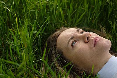 Ernste junge Frau im Gras - p1363m2122479 von Valery Skurydin