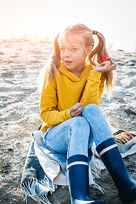 Portrait of girl with plaits sitting on the beach in autumn eating an apple - p300m2058897 von Epiximages