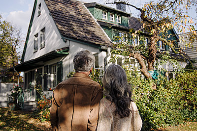 Rear view of senior couple in garden of their home in autumn - p300m2156242 by Gustafsson