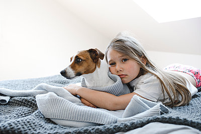 Cute girl embracing dog while lying on bed at home - p300m2275937 by Katharina Mikhrin