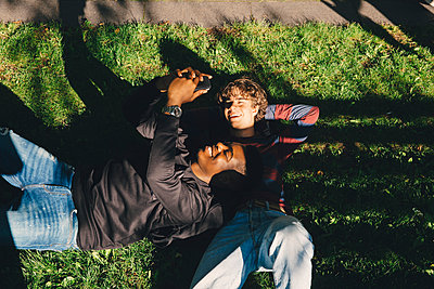 High angle view of smiling male friends taking selfie while lying on grass in park - p426m2217910 by Maskot