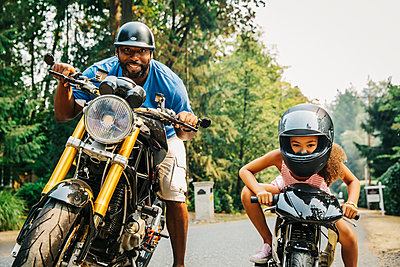 Father and daughter sitting on motorcycles - p555m1306242 by Inti St Clair