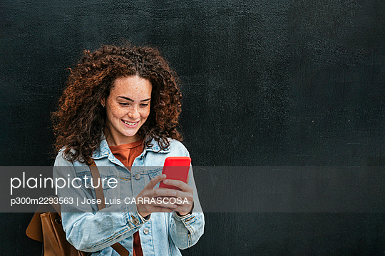 Smiling curly haired woman using smart phone while standing in front of black wall - p300m2293563 by Jose Luis CARRASCOSA