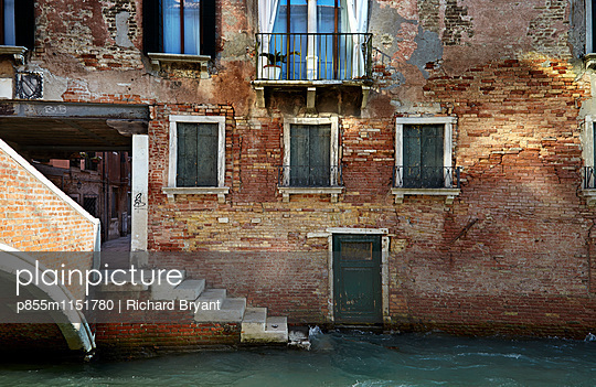Reflected light on canalside wall in Venice, Italy - p855m1151780 by Richard Bryant