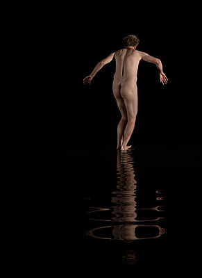 Naked man walks slowly on shallow water - p1132m2215550 by Mischa Keijser