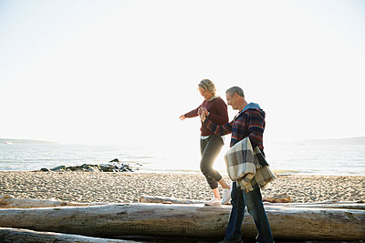 Couple holding hands walking balancing on driftwood on sunny beach - p1192m1149466 by Hero Images