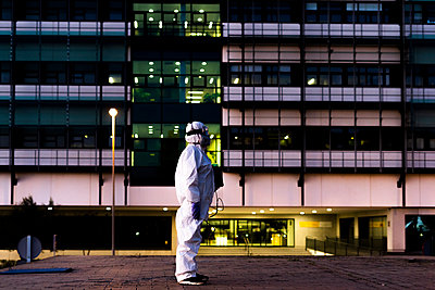Female scientist wearing protective suit and mask and standing in front of a laboratory - p300m2170110 by Eloisa Ramos
