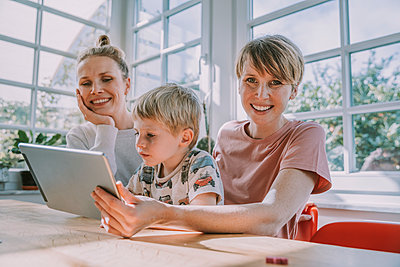 Happy mothers using digital tablet with son while sitting at home - p300m2226265 by Mareen Fischinger
