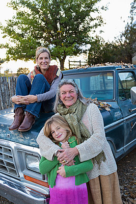 Three generations of Caucasian women sitting on truck - p555m1410476 by Marc Romanelli